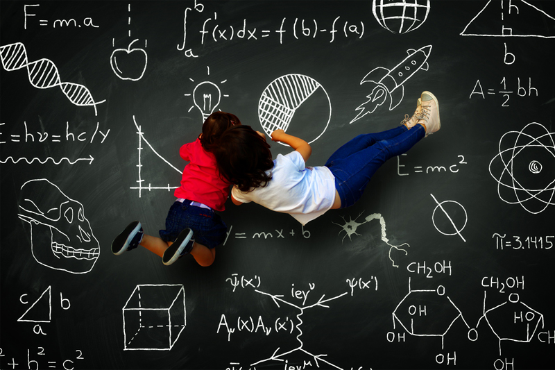 Two little writing girls on a blackboard with science subjects